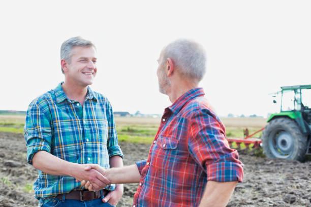Agricultor dándose la mano mientras está de pie en el campo - foto de stock