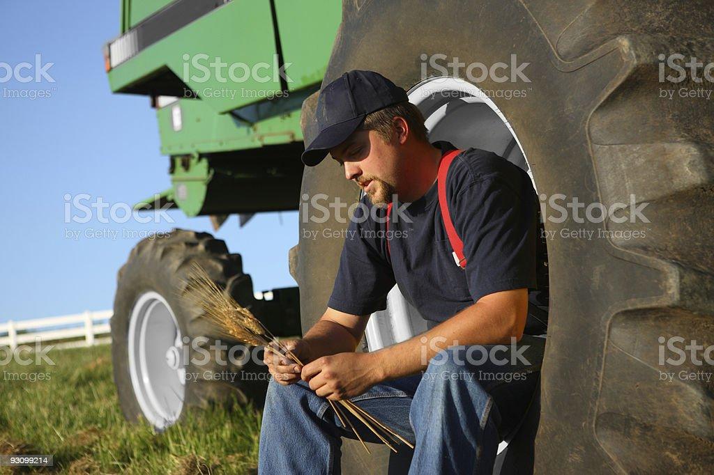 Farmer sitting in tractor wheel royalty-free stock photo