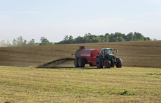 Farmer Spreading Liquid Manure Elmira, Ontario, Canada - June 1, 2016: Two tractors spreading liquid manure on a late spring day in Southwestern Ontario. spreading fertilizer stock pictures, royalty-free photos & images