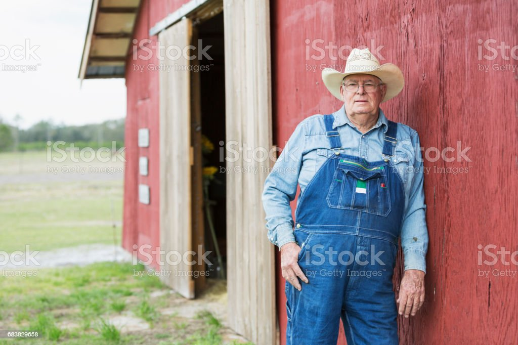 Farmer standing outside barn stock photo