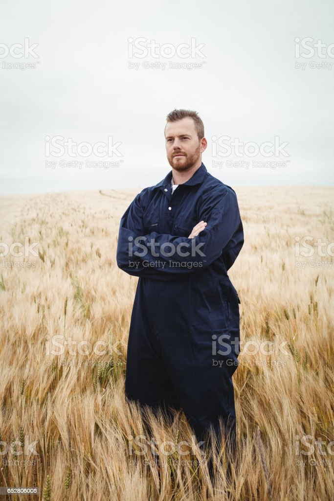 Farmer standing with arms crossed in the field stock photo