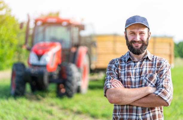 Farmer standing with arms crossed Farmer standing with arms crossed in front of tractor rancher stock pictures, royalty-free photos & images