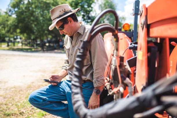 landwirt mit seinem smartphone während der ernte - waldhandwerk stock-fotos und bilder