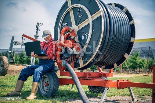 Farmer using laptop on the farm