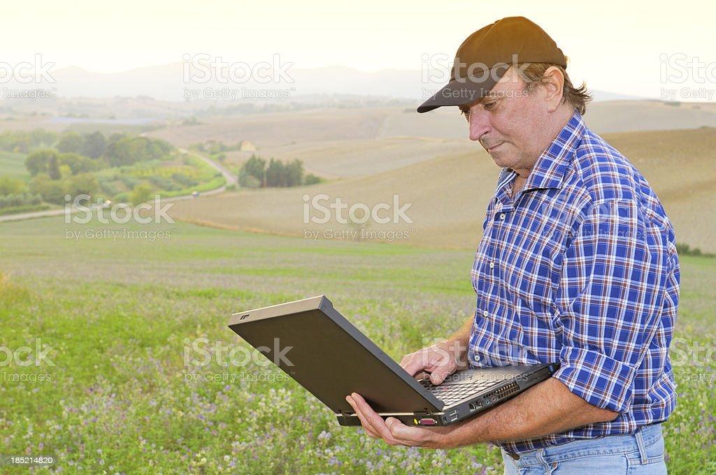 Farmer Using Old Laptop stock photo