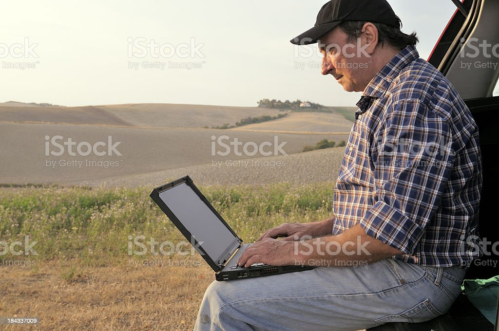 Farmer Using PC in the Countryside royalty-free stock photo