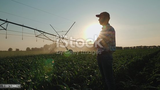 Silhouette of a farmer watching the irrigation of a cornfield using the center pivot sprinkler system at sunset. Watering a cornfield. Camera flies around a man in slow motion