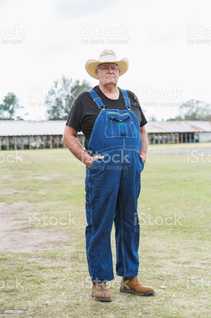 Farmer wearing overalls, barn in background stock photo
