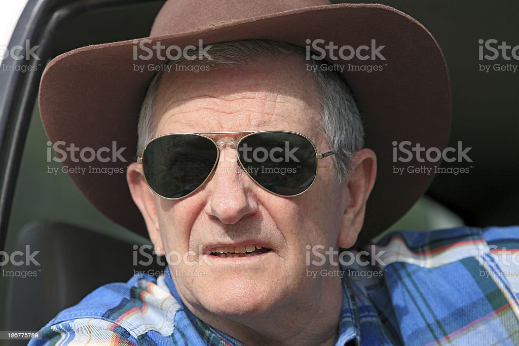 Farmer wearing sunglasses looking out of vehicle stock photo