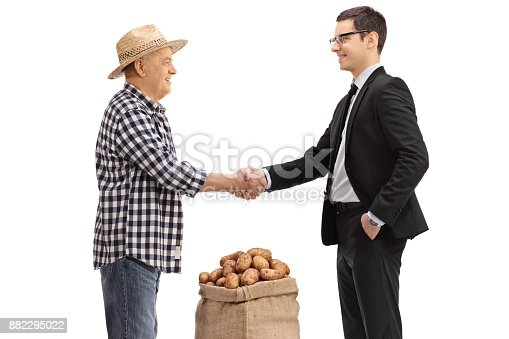 istock Farmer with a burlap sack filled with potatoes shaking hands with a businessman 882295022