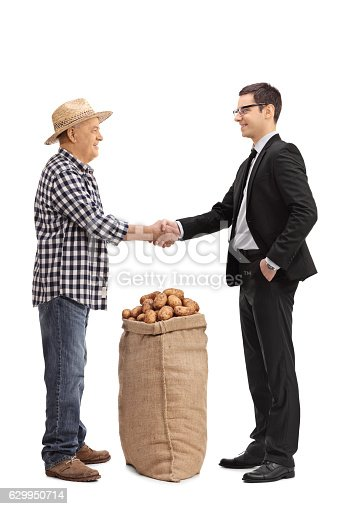 istock Farmer with a burlap sack shaking hand with a businessman 629950714