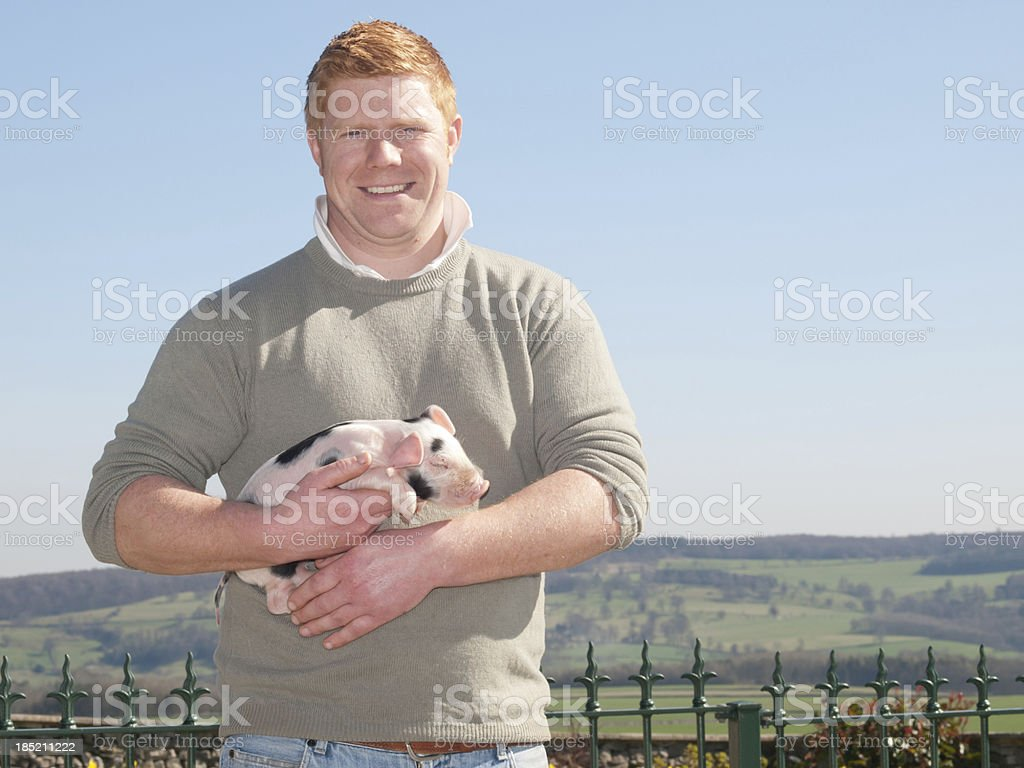 Farmer with a piglet stock photo