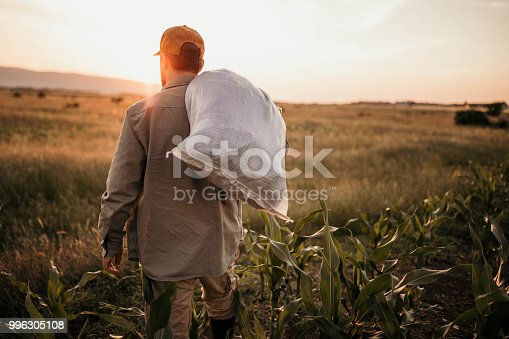 Photo of farmer with a sack on his back on his field