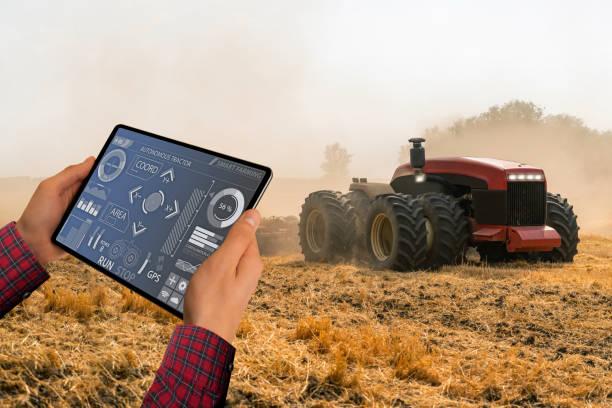 デジタルタブレットを持つ農家は、自律トラクターを制御します - リモート ストックフォトと画像