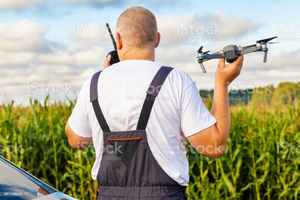 Farmer with drone at corn field stock photo