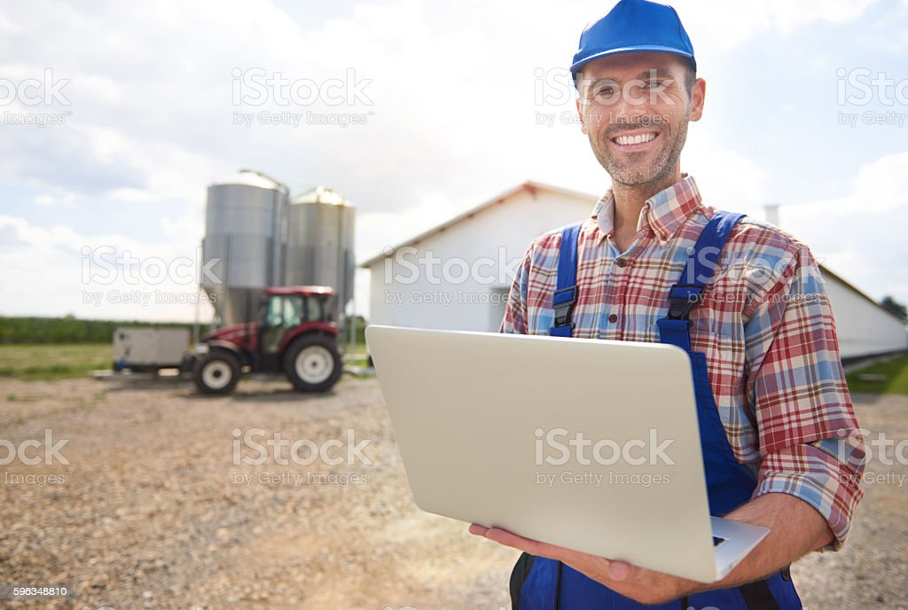 Farmer with laptop and his farm royalty-free stock photo