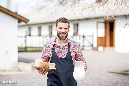 istock Farmer with milk and cheese outdoors 672369336