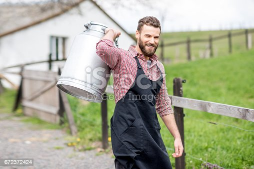 istock Farmer with milk outdoors 672372424