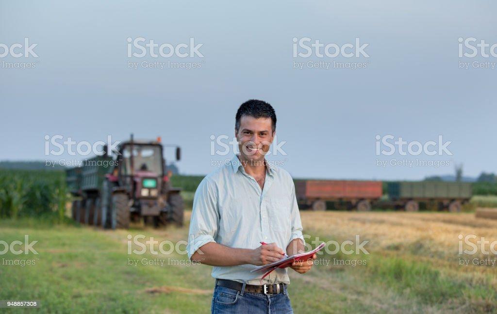Bauer mit Notebook vor Traktor im Feld – Foto