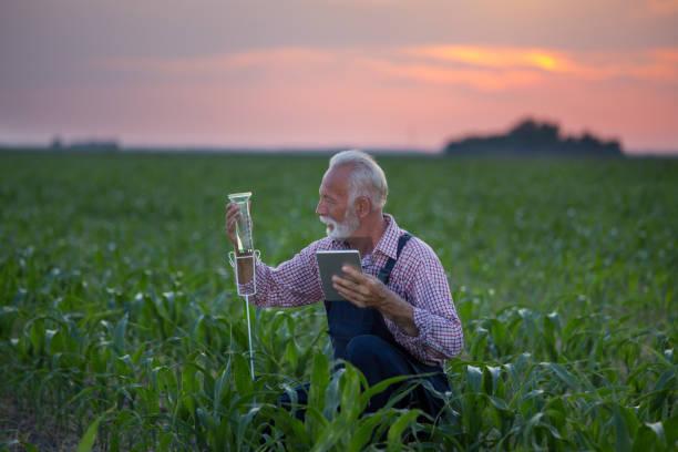 Landwirt mit Regenmessgerät im Feld – Foto