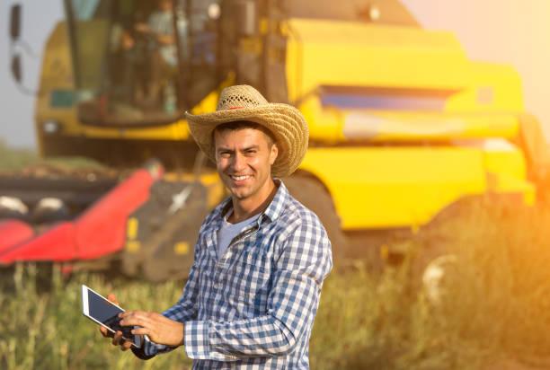 Bauer mit Tablet vor Mähdrescher – Foto