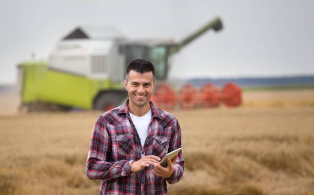 Bauer mit Tablet auf Feld bei der Ernte – Foto