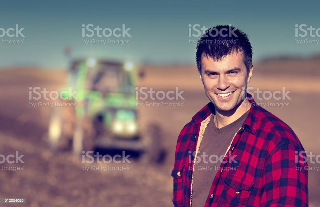 Farmer with tractor on field stock photo