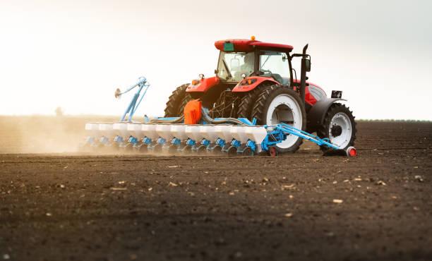 Landwirt mit Traktorsäen auf landwirtschaftlichem Feld – Foto