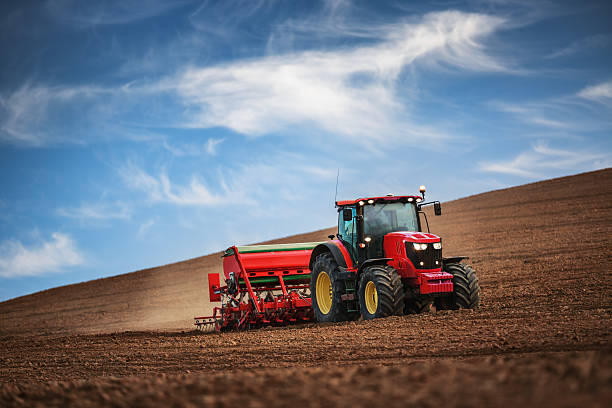 Farmer with tractor seeding crops at field Farmer in tractor preparing farmland with seedbed for the next year construction machinery stock pictures, royalty-free photos & images