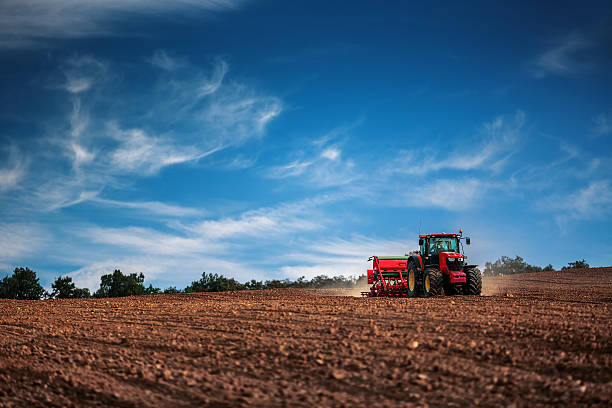 farmer with tractor seeding crops at field - zaaien stockfoto's en -beelden