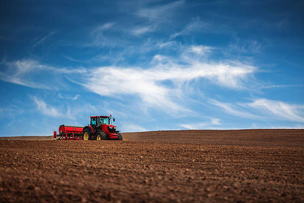 Farmer with tractor seeding crops at field Farmer in tractor preparing farmland with seedbed for the next year agricultural machinery stock pictures, royalty-free photos & images