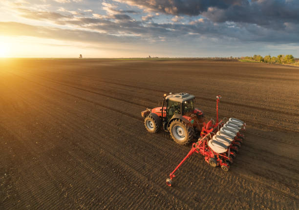 Farmer with tractor seeding - sowing crops at agricultural fields in spring Farmer with tractor seeding - sowing crops at agricultural fields in spring agricultural machinery stock pictures, royalty-free photos & images