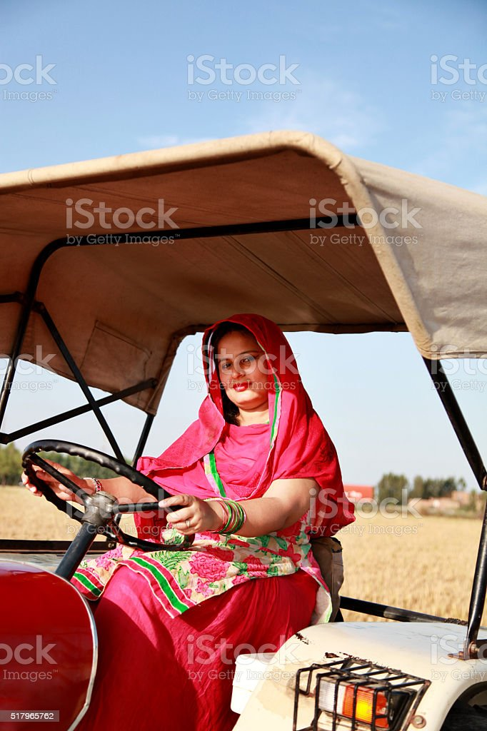 Farmer woman driving an old tractor through a field stock photo