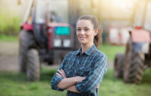 Farmer woman in front of tractors