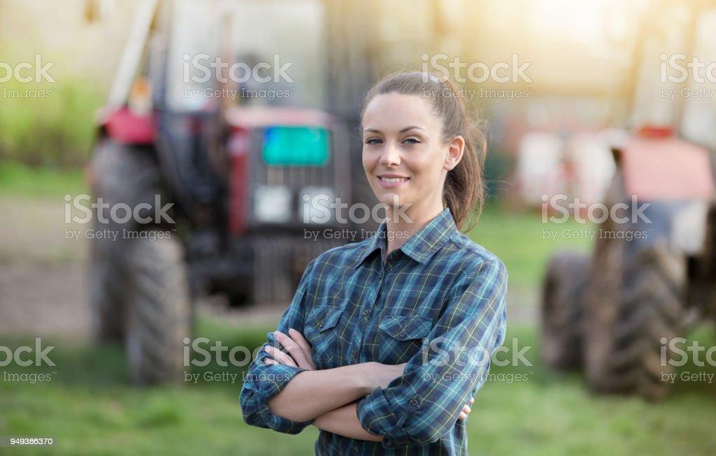 Femme d'agriculteur devant tracteurs - Photo