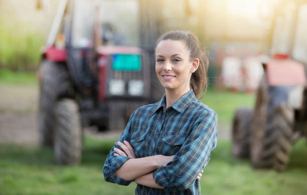 Farmer woman in front of tractors stock photo