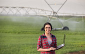 Pretty young farmer woman with laptop standing in front of irrigation system in field