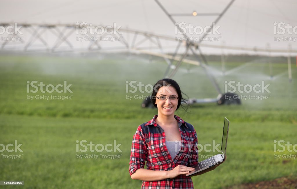 Farmer woman with irrigation equipment in field stock photo