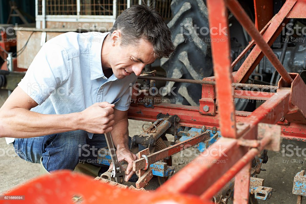 Farmer Working On Agricultural Equipment In Barn stock photo