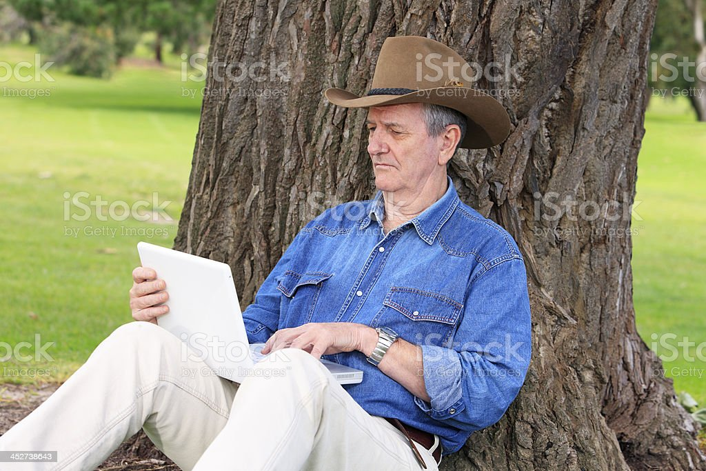 Farmer working on computer under shady tree stock photo