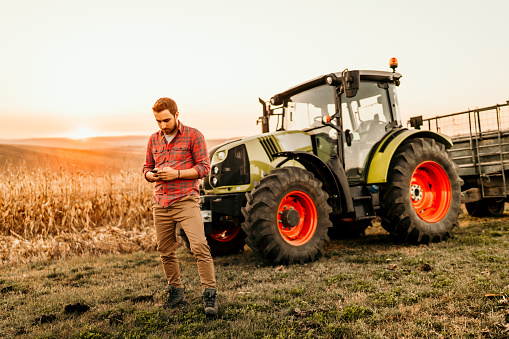 istock Farmer working on field using smartphone in modern agriculture 1076028764