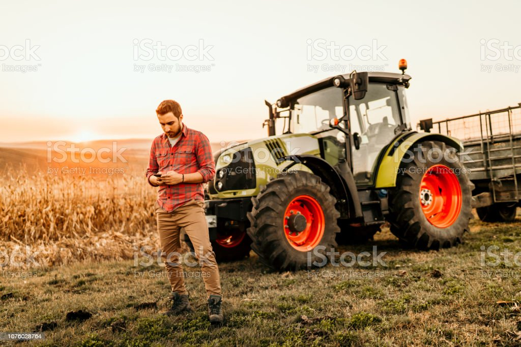 Farmer working on field using smartphone in modern agriculture stock photo