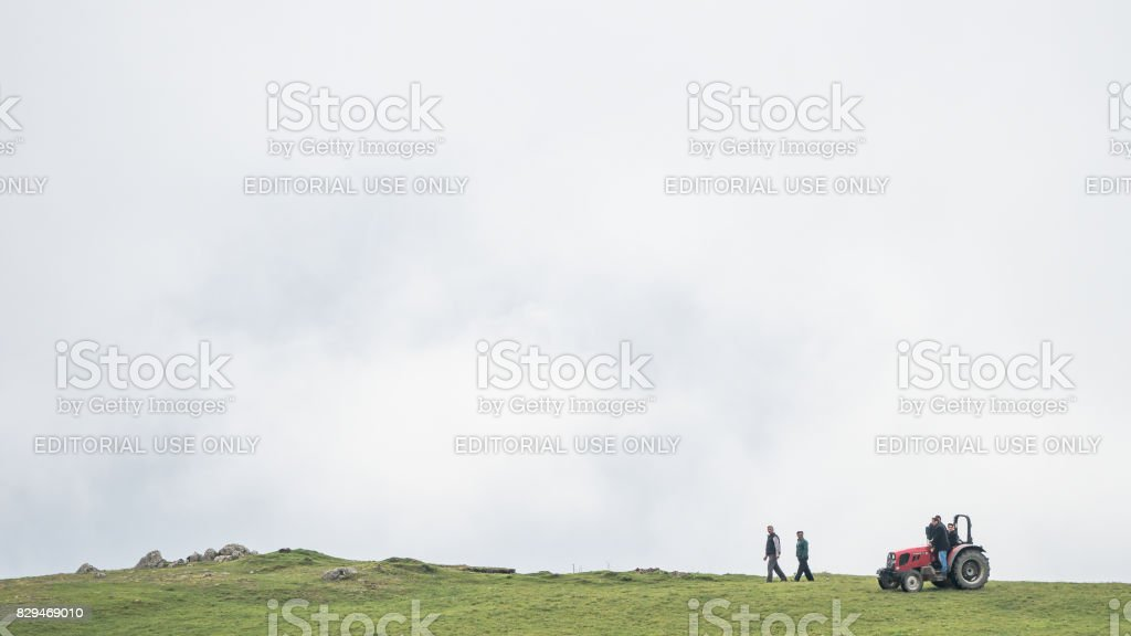 Farmers and a tractor on the top of a hill stock photo