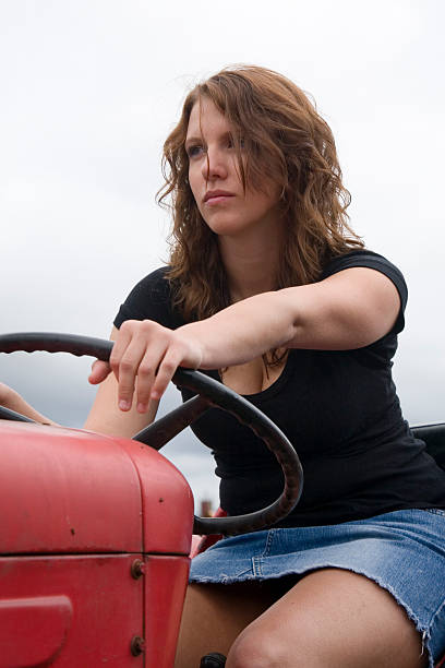 Farmer's daughter on tractor stock photo