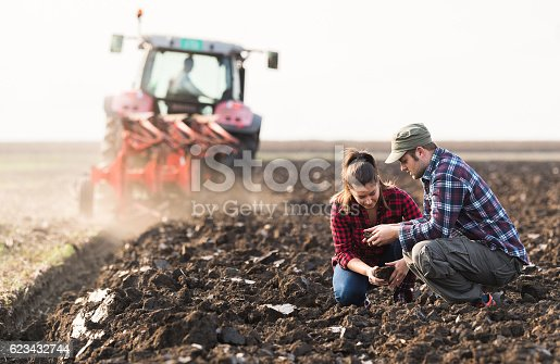istock Farmers examing dirt while tractor is plowing field 623432744