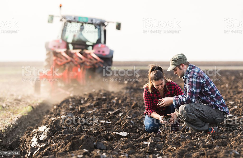 Farmers examing dirt while tractor is plowing field - foto stock