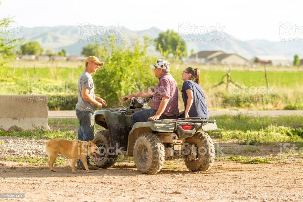 farmers family travel at atv vehicle at dairy farm in Utah USA