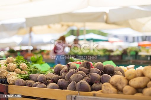istock Farmers' food market stall with variety of organic vegetable. Vendor serving and chating with customers 1175652956