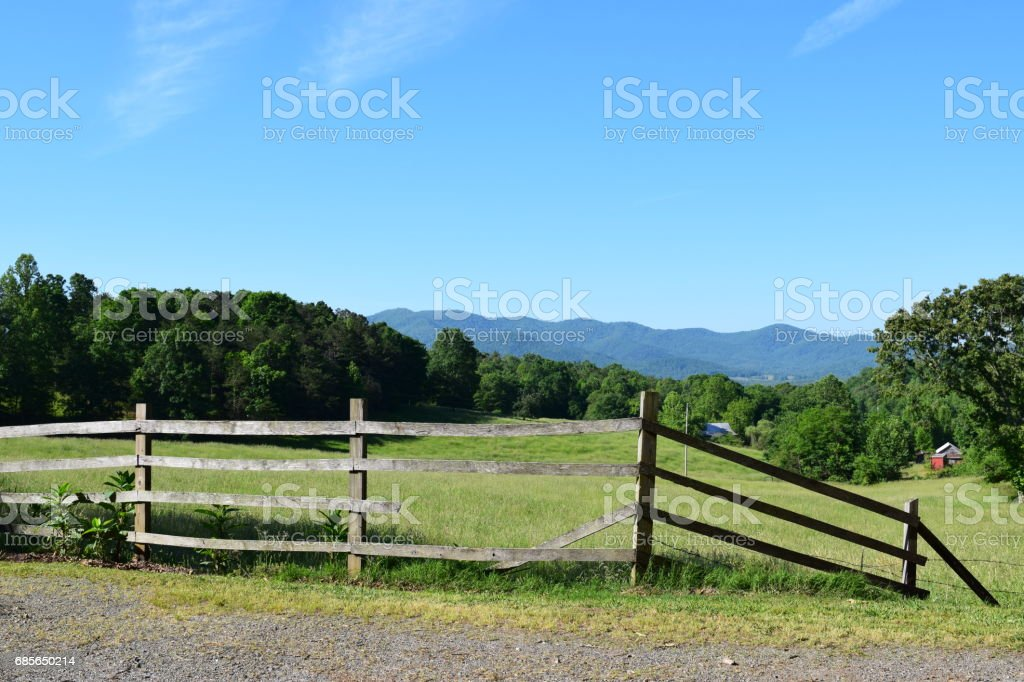 Farmer's grazing fenced field with mountains in the background stock photo