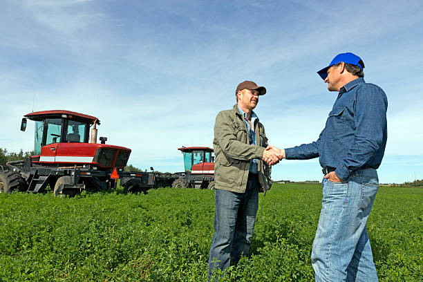 farmers handshake at a farm with tractors - farmer stock photos and pictures